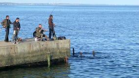 Pescadores que travam os peixes do cru do cais 4K processados video estoque