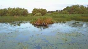 Pescadores que verificam redes no alvorecer no delta de Danúbio, vista aérea filme
