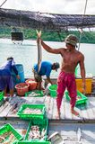 Pescadores tailandeses que clasifican captura del día en Tailandia Fotografía de archivo