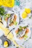 Pescados asados deliciosos de la brema del dorado o de mar con el limón y gambas frescas, perejil fresco y espinaca en el disco b imágenes de archivo libres de regalías