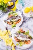 Pescados asados deliciosos de la brema del dorado o de mar con el limón y gambas frescas, perejil fresco y espinaca en el disco b fotos de archivo