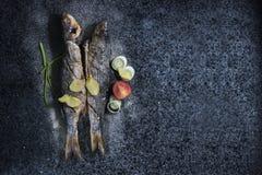 Pescados asados a la parrilla con las especias, las verduras y las hierbas en el fondo de la pizarra listo para comer fotos de archivo