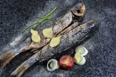 Pescados asados a la parrilla con las especias, las verduras y las hierbas en el fondo de la pizarra listo para comer foto de archivo