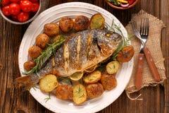 Pescados asados a la parrilla con las patatas y las verduras asadas en la placa imagen de archivo