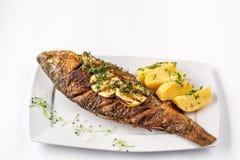 Pescados asados a la parrilla de la carpa con las patatas y el limón, cierre del romero para arriba Imagen de archivo