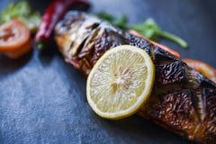 Pescados asados a la parrilla del saba con las especias dulces de la salsa y del limón con el fondo oscuro imagen de archivo