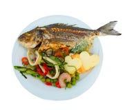 Pescados asados a la parrilla en la placa blanca con las hierbas queso y el aislante del camarón Imagen de archivo