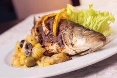 Pescados asados a la parrilla en una placa con el limón y las verduras Imagen de archivo