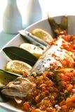 Pescados cocidos al horno con la salsa de tomate Imagen de archivo libre de regalías