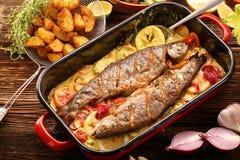 Pescados cocidos con la salsa y las verduras del limón en una cacerola Fotografía de archivo