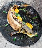 Pescados cocidos del esturión con romero, el limón y la fruta de la pasión en la placa en cierre de madera del fondo para arriba fotos de archivo
