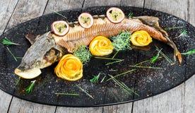 Pescados cocidos del esturión con romero, el limón y la fruta de la pasión en la placa en cierre de madera del fondo para arriba fotografía de archivo libre de regalías