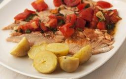 Pescados cocinados con las patatas y la salsa de tomate fotos de archivo