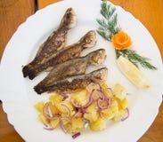 Pescados con la ensalada de patatas Fotos de archivo