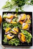Pescados crudos con las verduras y las hierbas en la cacerola Imagen de archivo