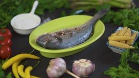 Pescados crudos frescos del dorada en un plato verde con el sistema de verduras en una tabla negra metrajes