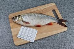 Pescados crudos, no cocinados Pescados blancos en una tabla de cortar y píldoras Imágenes de archivo libres de regalías