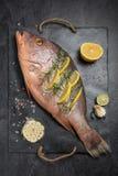Pescados crudos recientemente adobados con las rebanadas del limón, ajo del pargo rojo Fotos de archivo libres de regalías