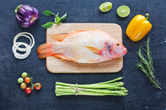 Pescados crudos y verduras en una tabla oscura Imagen de archivo
