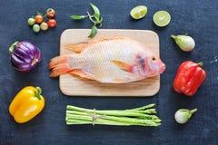 Pescados crudos y verduras en una tabla oscura Imagenes de archivo