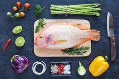 Pescados crudos y verduras en una tabla oscura Imagen de archivo libre de regalías