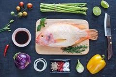 Pescados crudos y verduras en una tabla oscura Foto de archivo