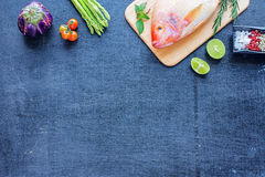 Pescados crudos y verduras en una tabla oscura Fotos de archivo libres de regalías