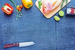Pescados crudos y verduras en una tabla oscura Imágenes de archivo libres de regalías