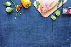 Pescados crudos y verduras en una tabla oscura Fotografía de archivo