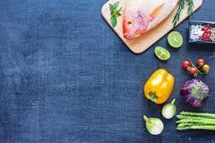 Pescados crudos y verduras en una tabla oscura Fotografía de archivo libre de regalías