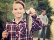 Pescados de agua dulce de la captura de la tenencia del muchacho en manos Imágenes de archivo libres de regalías