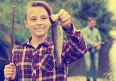 Pescados de agua dulce del adolescente de la captura relajada de la tenencia Foto de archivo libre de regalías