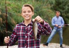 Pescados de agua dulce sonrientes de la captura de la tenencia del adolescente Imagenes de archivo