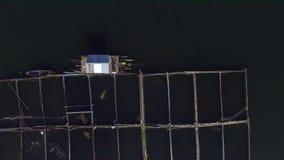 Pescados de alimentación del pescador en las jaulas de bambú en el lago de la montaña Tiro de la antena del abejón metrajes