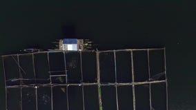 Pescados de alimentación del pescador en las jaulas de bambú en el lago de la montaña Tiro de la antena del abejón almacen de video