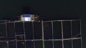 Pescados de alimentación del pescador en las jaulas de bambú en el lago de la montaña Tiro de la antena del abejón almacen de metraje de vídeo