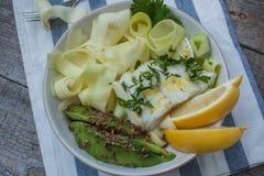 Pescados de bacalao con las pastas cocidas al vapor del calabacín, aguacate Foto de archivo