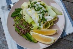 Pescados de bacalao con las pastas cocidas al vapor del calabacín, aguacate Imágenes de archivo libres de regalías