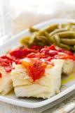 Pescados de bacalao hervidos con la pimienta roja y las habas verdes Foto de archivo libre de regalías