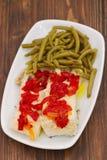 Pescados de bacalao hervidos con la pimienta roja y las habas verdes en plato Imagenes de archivo