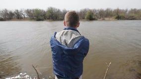 Pescados de cogida del pescador y carrete de giro de la pesca en el agua de río del fondo almacen de video