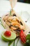 Pescados de color salmón cocidos en la hoja de papel Foto de archivo