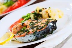 Pescados de color salmón cocinados en la placa Fotografía de archivo