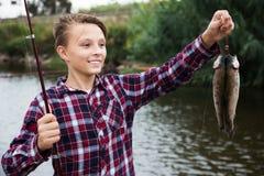Pescados de la captura de la demostración del muchacho de Fisher Fotos de archivo