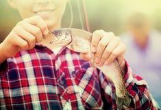 Pescados de la captura de la tenencia del muchacho del adolescente en el gancho Foto de archivo libre de regalías