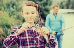 Pescados de la captura de la tenencia del muchacho del adolescente en el gancho Imágenes de archivo libres de regalías