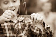 Pescados de la captura de la tenencia del muchacho del adolescente en el gancho Imagen de archivo