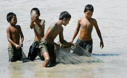 Pescados de la captura de los niños en campo de arroz Foto de archivo libre de regalías