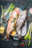 Pescados de la trucha y trucha arco iris enteros crudos del oro en plato en plato con los cubos de hielo y los ingredientes de co Foto de archivo libre de regalías