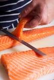 Pescados de los salmones del corte del cocinero Fotografía de archivo libre de regalías